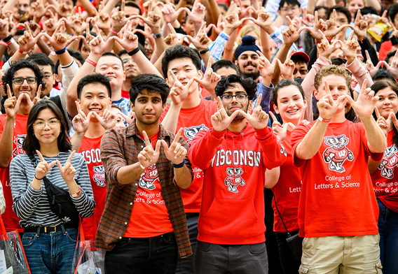 Large group of University of Wisconsin students holding up their hands to create the shape of a W with their fingers.
